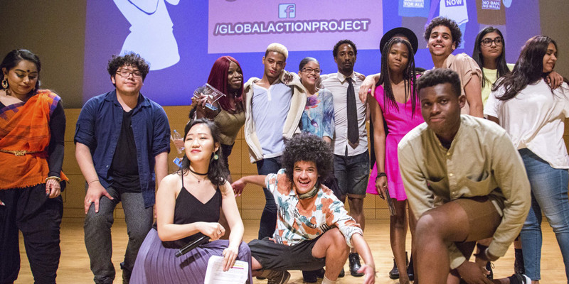A multiracial group of a dozen young people posing on a stage in front of a screen with Global Action Project on it