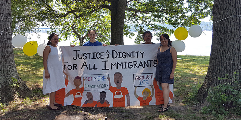 """Four people stand around a sign hanging between two trees that says """"Justice & Dignity For All Immigrants"""""""