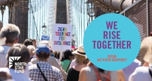 A large crowd of people walking on the Brooklyn Bridge with protest signs