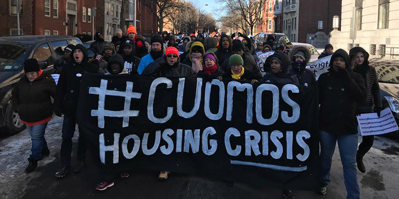 Folks marching with a huge banner in front of them that reads #CuomosHousingCrisis