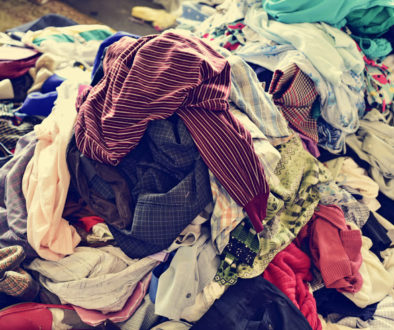closeup of a pile of different used clothes on sale in a flea market, with a filter effect