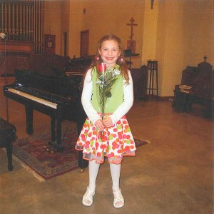 Lillie, smiling after completing her first-ever piano recital.  Lillie received a piano with the assistance of Redding Piano Angels.