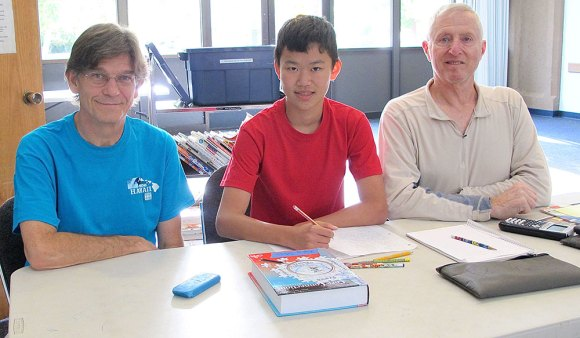 Jonathan Jordan and Mike St. John, both former educators, work with student Xing Shen, a Chico High School student, during the Chico Branch Library's Homework Help drop-in program.