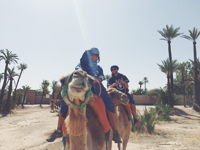 Chris Tyre and Ismary Torres riding camels in Morocco