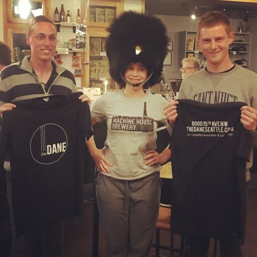Kelly, co-owner of The Dane, standing between the two Danish Royal Guards, wearing their bearskin hat. They went home with free t-shirts for their surprise performance.
