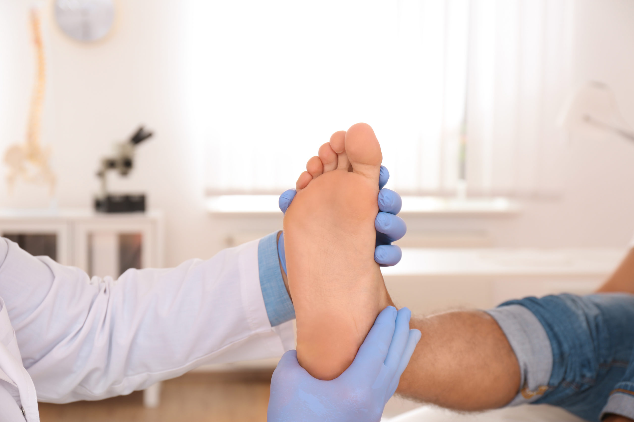 A man in the middle of bunion recovery has his foot examined by his surgeon.