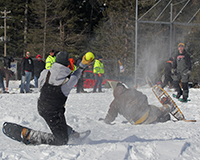 Players in the snowshoe baseball game falling on the ground while throwing the baseball to home plate
