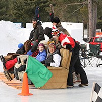 Recliner race participants four teams lined up at the starting line ready to push recliners on skis down ice track