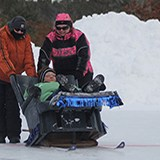 Three people all dressed up for cold weather two pushing a person in a recliner chair with skis on the bottom in a race on ice