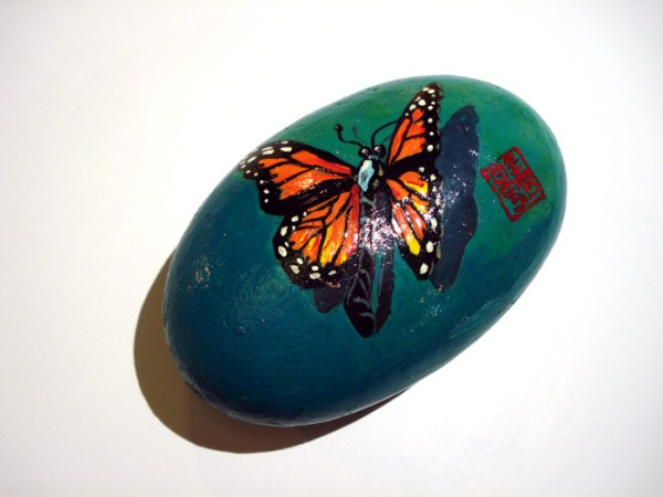 small blue stone with orange and yellow butterfly painted on it