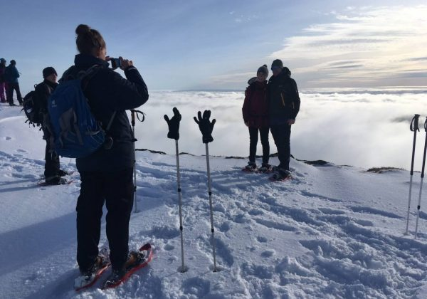 Tourists taking pictures from the top of Mount Ulriken on the Snowshoe trip