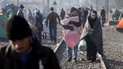 Migrants walk along railway tracks at the Greek-Macedonian border, near the village of Idomeni,