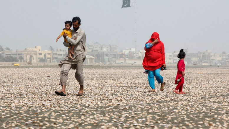 A woman covers her face with scarf to avoid heat while walking with her family along the beach on a hot summer day in Karachi, Pakistan
