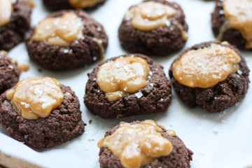 a baking tray full of salted caramel chocolate thumbprint cookies