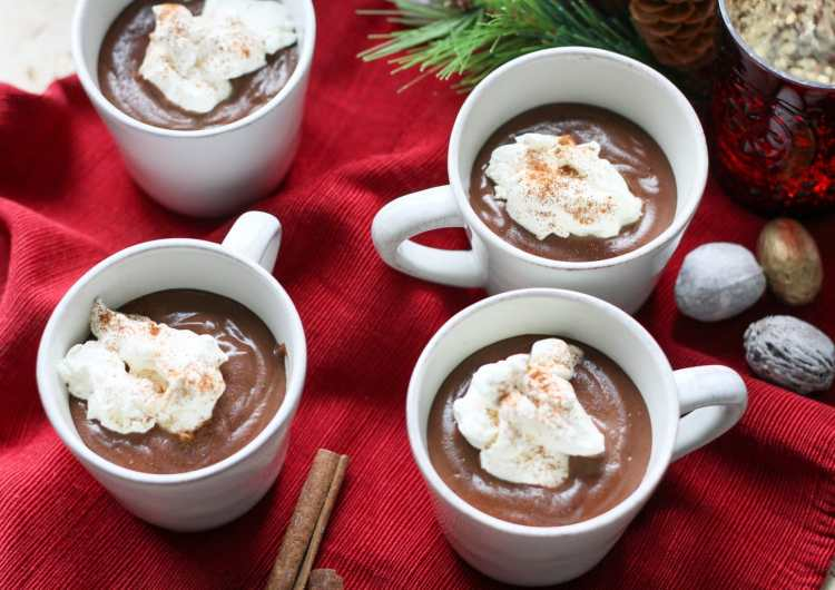 white mugs filled with chocolate pudding on a red napkin