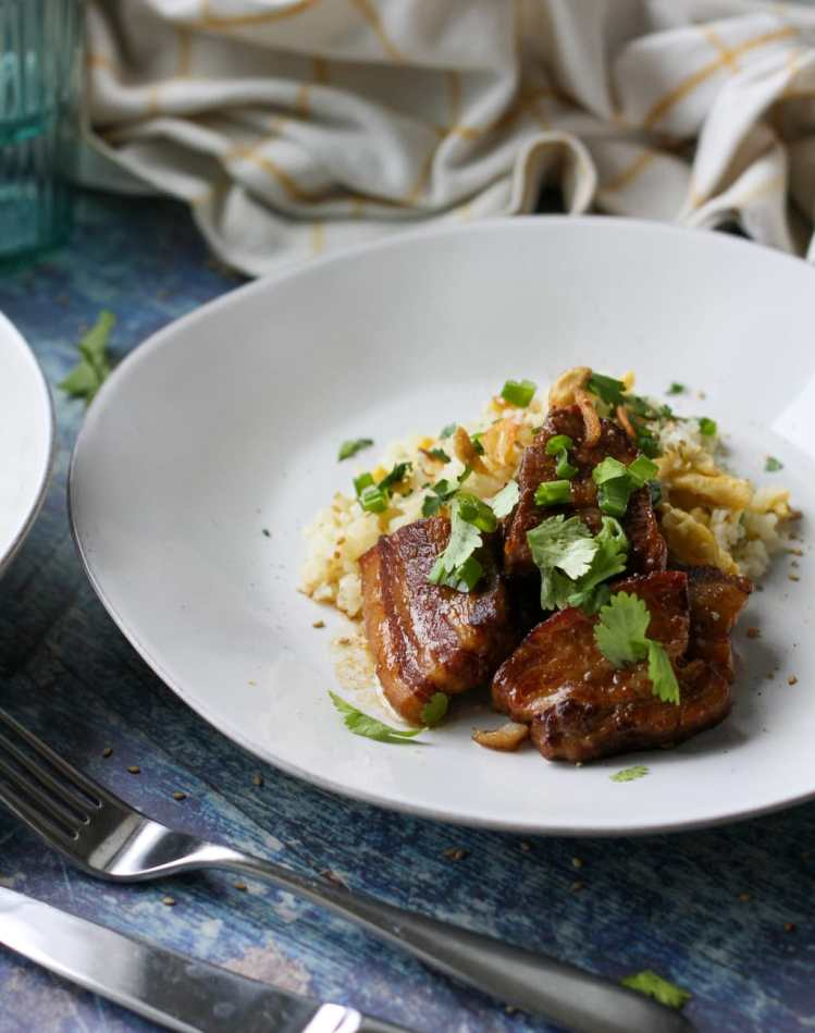 three slabs of pork belly adobo with garlic rice on a white plate