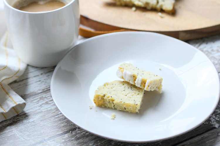 a slice of keto lemon poppy seed bread on a plate with a cup of coffee
