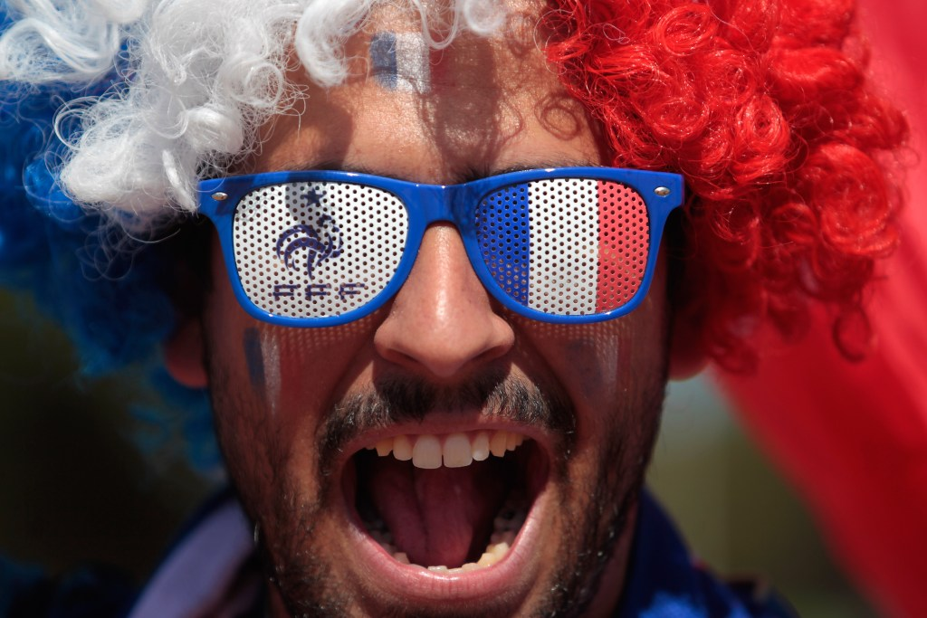 A France soccer fan, with his face painted with the team's colors arrives at the National Stadium to watch World Cup round of 16 match against Nigeria, in Brasilia, Brazil, Monday, June 30, 2014. France's Paul Pogba scored with a late header to finally break Nigeria's stubborn resistance and Joseph Yobo scored an own-goal as France won 2-0 to reach the World Cup quarterfinals on Monday. (AP Photo/Eraldo Peres)