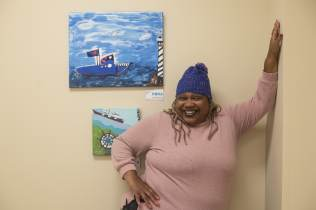 Gwen Johnson (Gigi) standing next to her artwork.