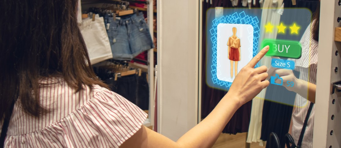 iot smart retail futuristic technology concept, happy girl try to use smart display with virtual or augmented reality in the shop or retail to choose select ,buy cloths and give a rating of products