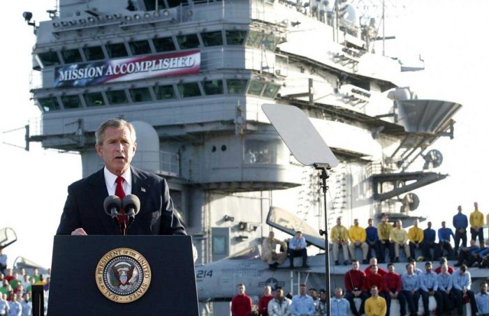 "From aboard the aircraft carrier USS Abraham Lincoln on May 1, 2003, standing directly under a ""Mission Accomplished"" banner, President George W. Bush declares, ""In the battle of Iraq, the United States and our allies have prevailed."""