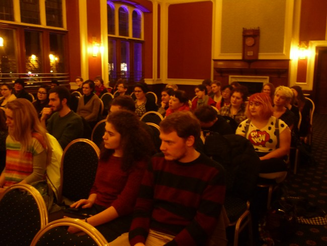 An audience sit in a function room, in rows of chairs. They are watching and listening intently.