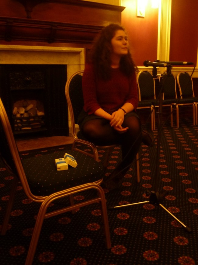 Young woman sits talking into microphone in front of her. She is in a function room. Fireplace behind her.