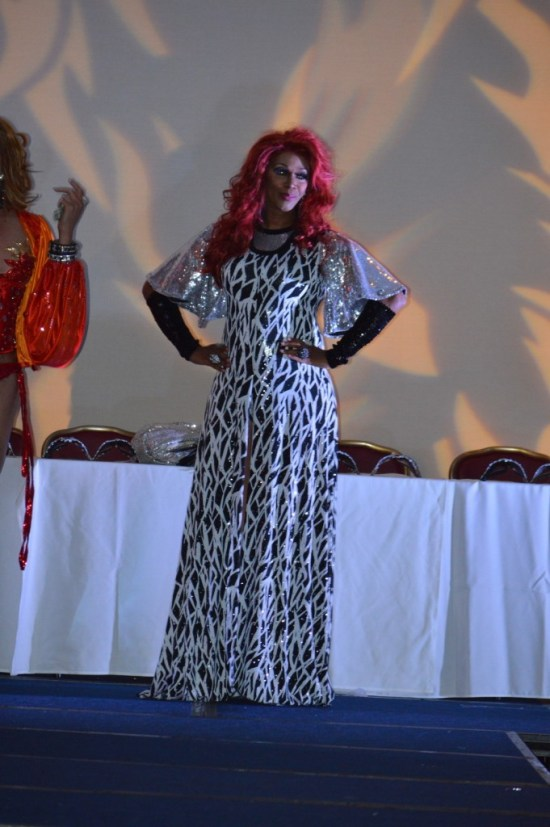 Performer in full length sparkly black and silver gown. Hands on hips. Big red hair.