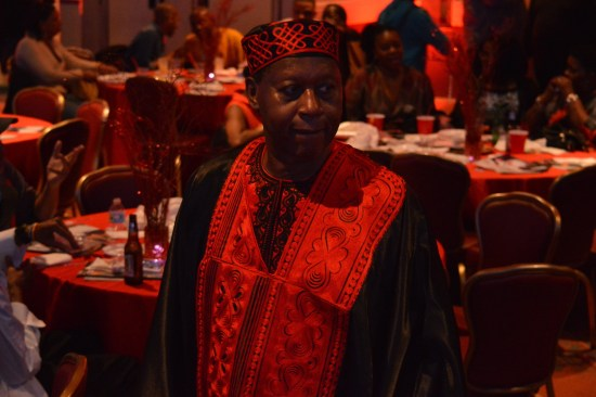 James Credle in traditional African clothing. At the Fireball event, standing in front of cabaret style tables.