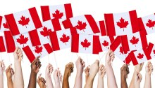 Mains qui tiennent des drapeaux canadiens