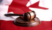 Gavel sitting on top of a Canadian flag