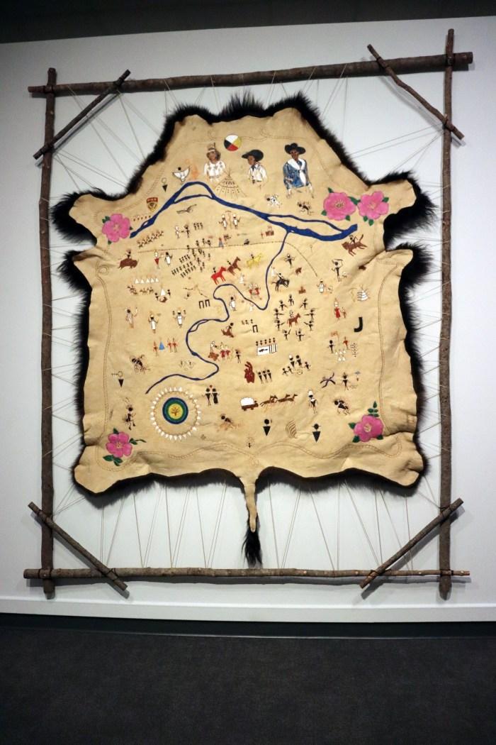 L'image représente une carte, fixée dans un cadre, intitulée « First Nations Stampede: A Guide to First Nations History at the Calgary Stampede » par l'artiste Adrian Stimson.