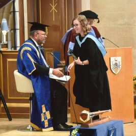 Daisy graduating from her MPhys degree with a focus on quantum physics. She is wearing a black graduation gown with a light blue trim and is about to shake the hand of the Chancellor.