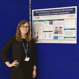 Daisy standing with her poster on quantum physics of quantum point contacts at the UK semiconductors conference. She is wearing a black dress and blazer and her poster is on a dark blue poster board.