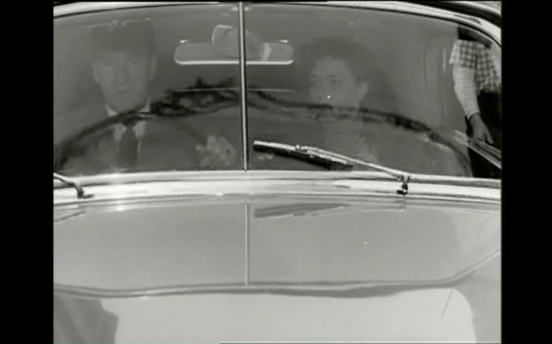 Reflections on the windshield, a world outside the car, in Rossellini's Journey to Italy.