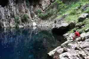 Man contemplating the water in Chinhoyi Caves National Park, Zimbabwe (2012-04)