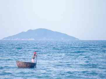 Fisherman with traditional round boat off the beach, Hoi An, Vietnam (2017-05/06)