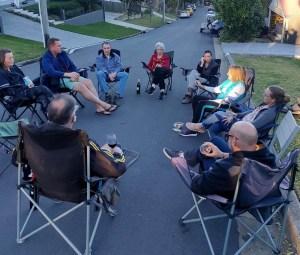 Group of neighbours socialising in cul de sac.
