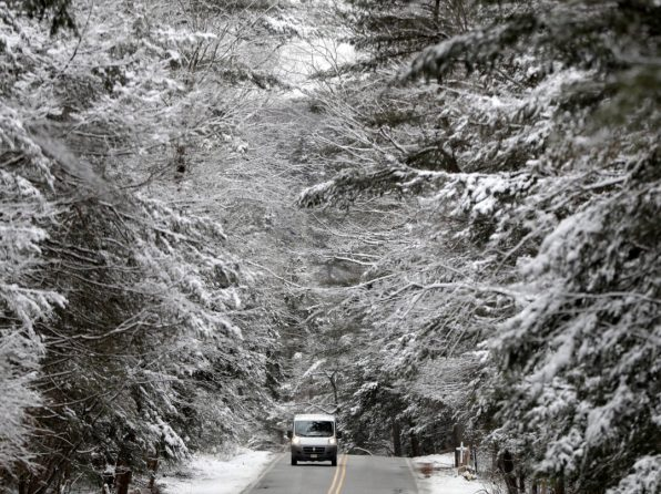A vehicle rides along Clinton Road in Hewitt, N.J., Wednesday, Jan. 30, 2019. A fast-moving snowstorm moved through the northern New Jersey Wednesday afternoon. Temperature is predicted to dip into the single digits overnight. (AP Photo/Julio Cortez)