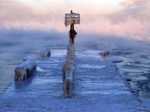 A harbor light is covered by snow and ice on the Lake Michigan at 39th Street Harbor, Wednesday, Jan. 30, 2019, in Chicago. A deadly arctic deep freeze enveloped the Midwest with record-breaking temperatures on Wednesday, triggering widespread closures of schools and businesses, and prompting the U.S. Postal Service to take the rare step of suspending mail delivery to a wide swath of the region. (AP Photo/Nam Y. Huh)