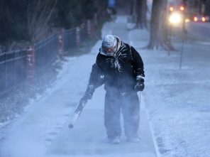 James Dusenbery blows a dusting snow off the sidewalk in Englewood, N.J., Wednesday, Jan. 30, 2019. The National Weather Service issued blizzard warnings for sections of upstate New York on Wednesday and officials urged people to stay inside as heavy, wind-driven snow caused whiteout conditions amid subzero windchills. (AP Photo/Seth Wenig)