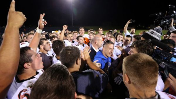 O treinador e seus atletas em oração após uma partida