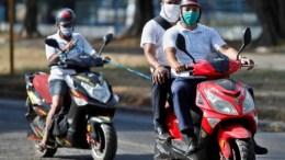 Cubanos en moto por las calles de La Habana