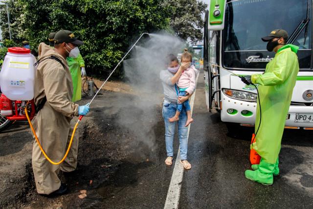 Migrantes venezolanos son desinfectados al bajar de los buses