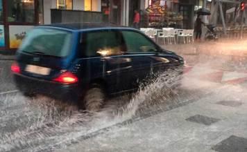 Un vehículo cruza Paseo de la Constitución de Arnedo durante la tormenta