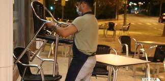 Un camarero desmontando una terraza por la noche en Arnedo