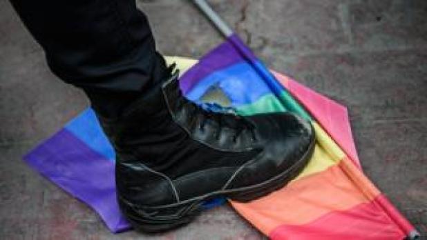 un Turco antidisturbios Policía pasos fuera una bandera del arco iris durante un mitin organizado por la comunidad LGBT en Estambul (19 de junio de 2016)