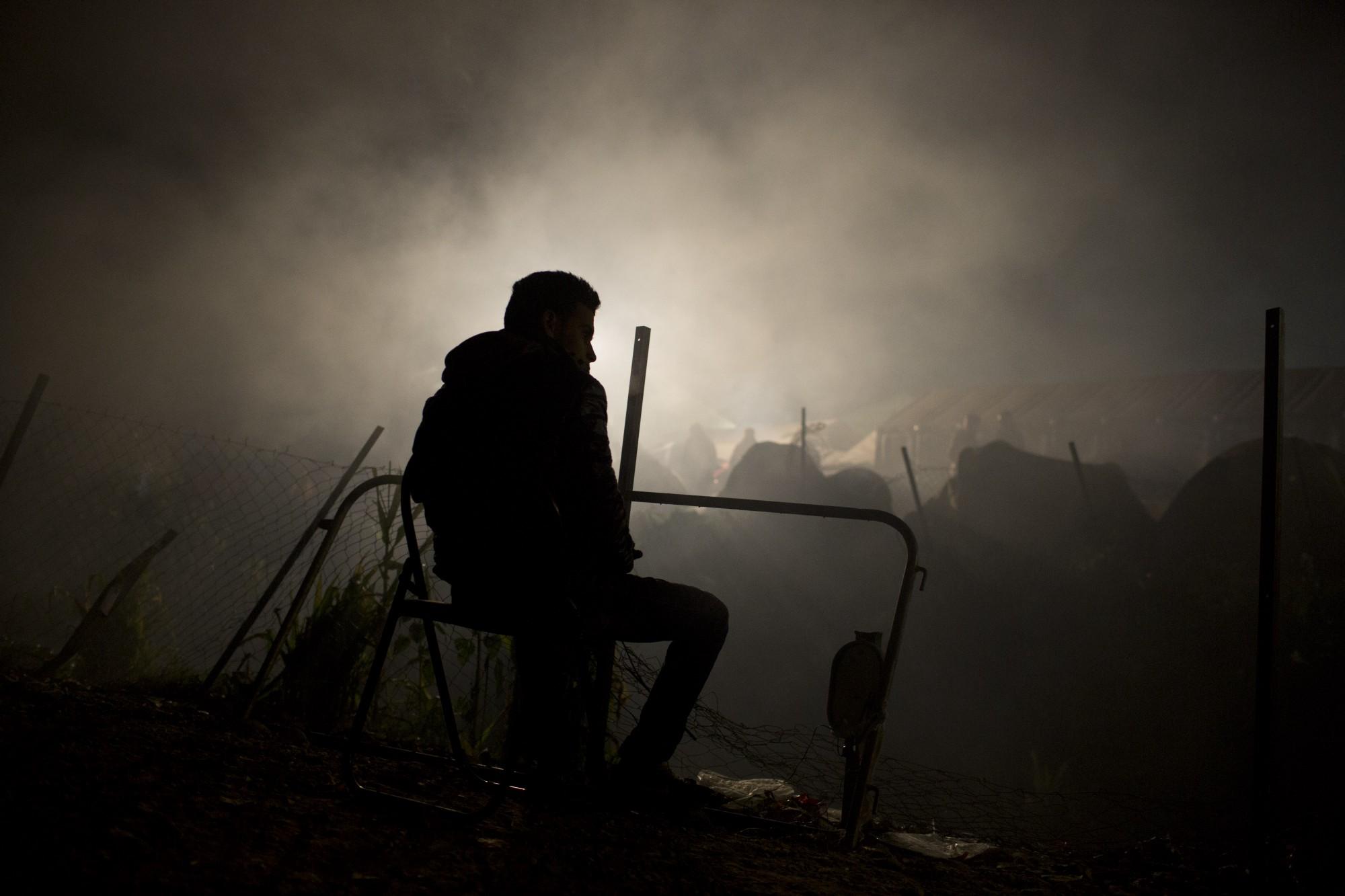 Un migrante sentado cerca de un fuego en un campamento de refugiados en la frontera de Grecia y Macedonia, donde llevaba esperando 17 días.