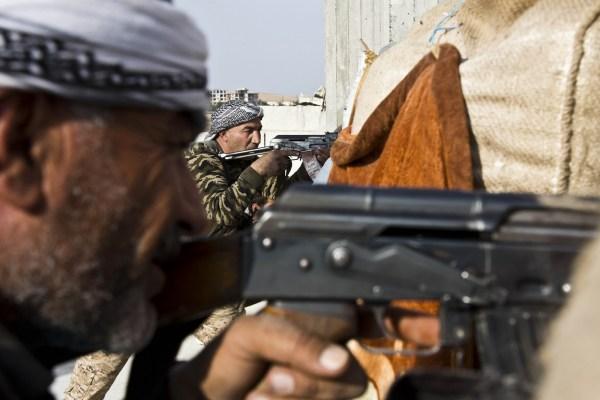 Soldado del Ejército Libre Sirio (izquierda) y de las fuerzas kurdas, Unidades de Protección Popular (centro), se unen en un enfrentamiento contra el Estado Islámico en noviembre del 2014.
