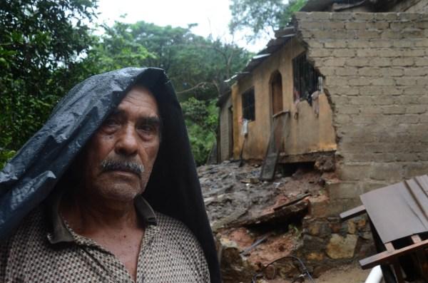 Un hombre de la comunidad Papa Gallo de Tierra Colorada en las cercanías de Acapulco, se para junto a su casa que fue afectada por el Huracán Manuel y en el momento de la foto por el Huracán Raymond.
